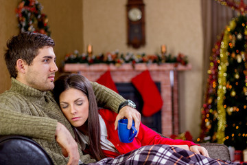 young romantic couple lying on the sofa in Christmas night