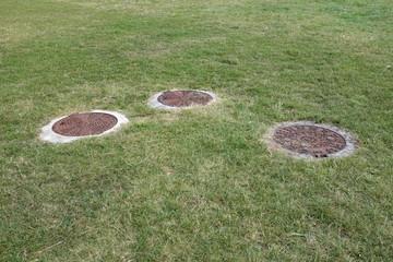 Trois plaques d'égout sur pelouse