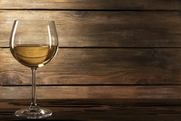 Goblet of white wine on wooden table on wooden wall background