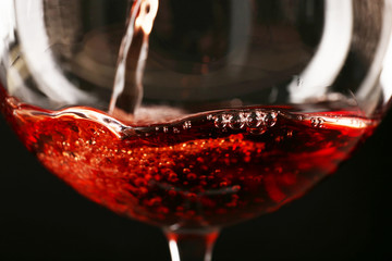 Glass of red wine on dark background closeup