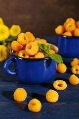 Yellow raspberries in dark blue mugs and wildflowers