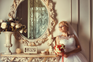 Portrait of blonde bride near the mirror