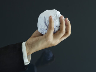 Ball of paper in hand on dark background, business concept