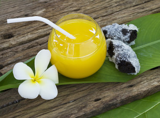 Fresh orange juice and donut on the leaf and wooden