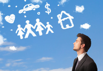 Businessman daydreaming with family and household clouds