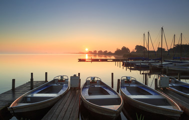 Foggy and tranquil sunrise at a small marina.