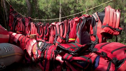 lifejackets are drying on a rope after rafting.