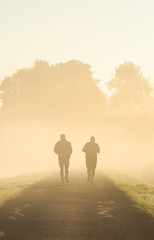 Two men running in the morning fog.