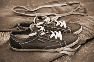 Black Sneakers and jeans with suspenders. Photo toning in sepia
