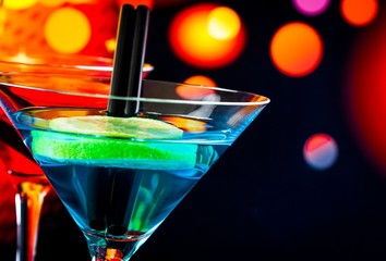 blue cocktail with light disco bokeh background