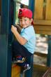 Little boy in cap climb up