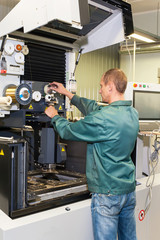 Worker operating industrial cnc machine in workshop