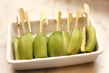 kiwi  fruits on skewers in white cup.