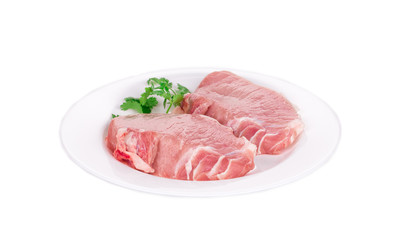 Raw pork steaks on plate.