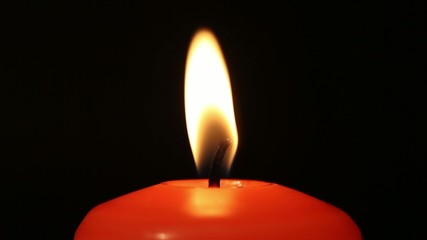 Close-up of burning candle on black background