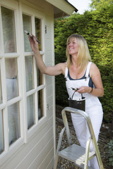 Painter decorator painting windows standing on steps