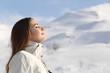Leinwanddruck Bild - Explorer woman breathing fresh air in winter in a snowy mountain