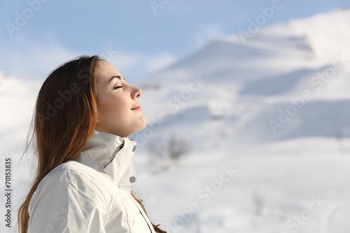 Leinwanddruck Bild Explorer woman breathing fresh air in winter in a snowy mountain