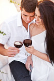 Tenderness couple with wine on sunset beach poster