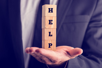Businessman holding wooden blocks saying Help