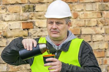 Construction Engineer drinking tea near stone wall