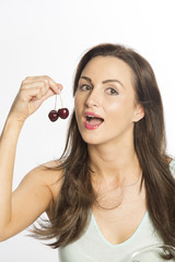 Attractive woman eating cherries