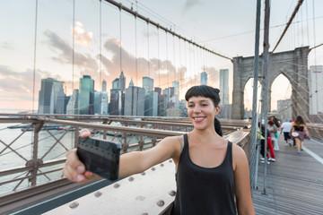 Pretty Young Woman Taking Selfie on Brooklyn Bridge