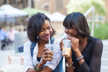 Two Beautiful Black Woman Enjoying Refreshing Drinks in New York