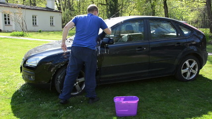 manual hand car wash cleaning with foam and sponge on open air.