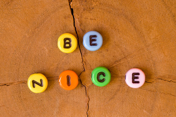 Colored be nice on wooden background