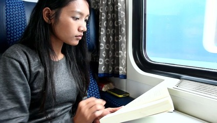Passenger read book while traveling by train