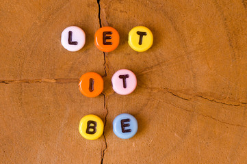 Colored let it be on wooden background