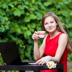 Красивая девушка с ноутбуком на природе