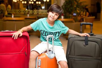 Мальчик сидит на чемоданах едет в путешествие