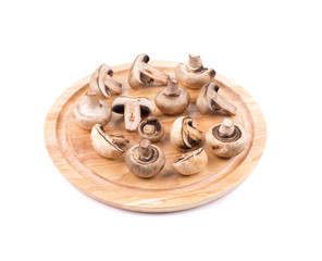 White mushrooms on wooden board.