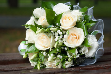 Wedding bouquet of cream roses and green leaves on wooden bench