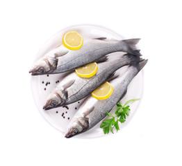 Three fresh seabass with lemon on plate.