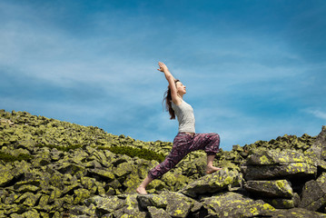 Woman doing yoga exercise on fresh air with blue sky on backgrou