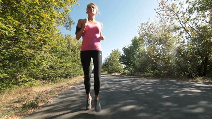 Woman fitness jogging workout on countryside road
