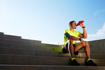 Handsome male runner seated on the steps drink water