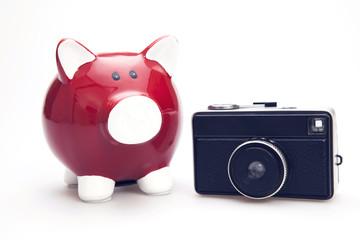 Red piggy bank with retro camera