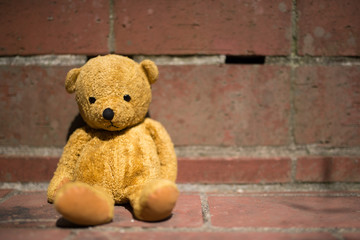 レンガの壁に寄りかかる熊の縫い包み