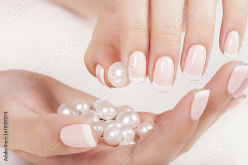 Beautiful woman's nails with french manicure and pearls. - 70159274