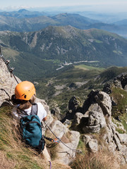 Climbing sport: caucasian young boy takes a rest observing the m