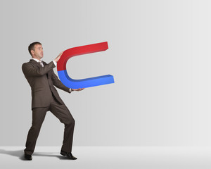 Businessman in suit holding big magnet