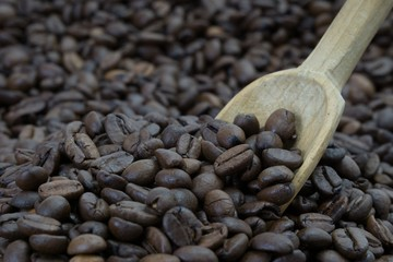 Old wooden spoon placed in a pile of coffee beans