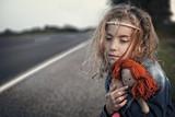 Desperate little girl orphan hugging a doll poster
