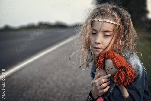 Leinwanddruck Bild Desperate little girl orphan hugging a doll
