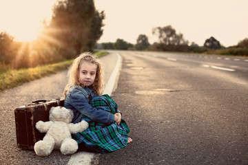 Lonely child with a suitcase and a teddy bear on road