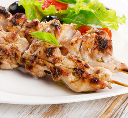 Grilled chicken kebab on a white plate